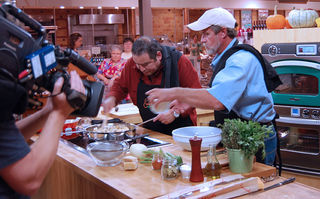 Tommy Leggett (wearing the hat), CBF's oyster and fisheries scientist in Virginia, cooks oyster stuffing with chef Emeril Lagasse. Cameras film the scene at Whole Foods Market in Fairfax, VA, for the cooking show, Emeril Green.