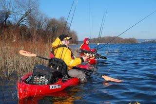 Fishing guides Juan Veruete (left) and Jeff Little (right) seek shelter from wind on the Susquehanna River