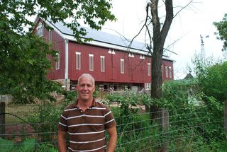Will Morrow in front of barn with solar panels